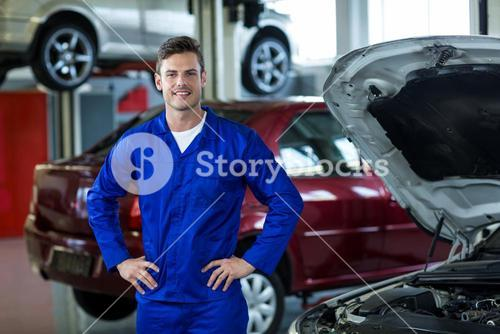 Mechanic standing with hands on hip in repair shop