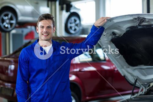Mechanic standing near car in repair shop