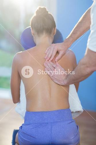 Physiotherapist giving back massage to a female patient