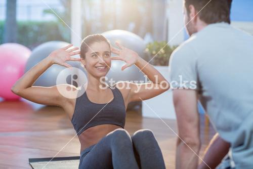 Physiotherapist assisting a female patient while exercising