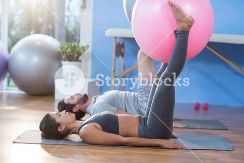 Man and woman holding exercise ball between legs