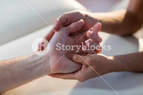 Physiotherapist giving hand massage to patient