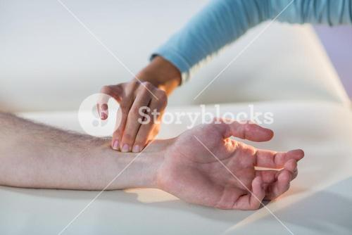 Therapist checking patient pulse