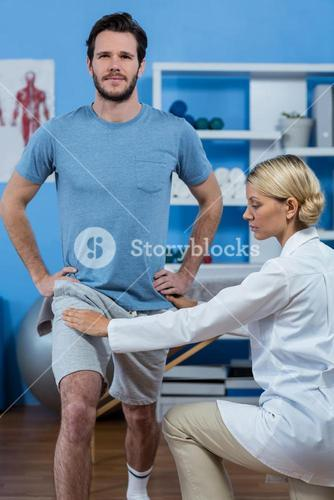 Physiotherapist assisting patient while exercising