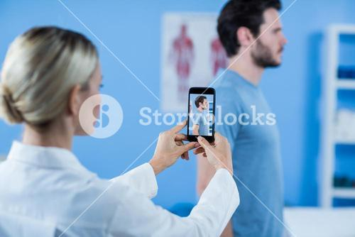 Physiotherapist clicking photo of a male patient