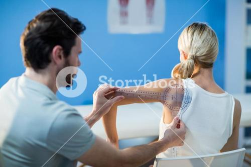 Male therapist measuring female patient shoulder with goniometer