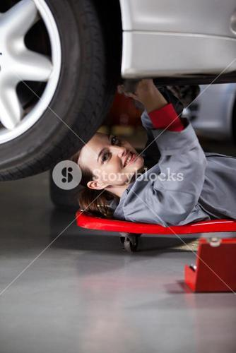 Portrait of female mechanic repairing a car