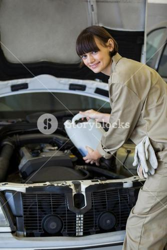 Female mechanic pouring oil lubricant into the car engine
