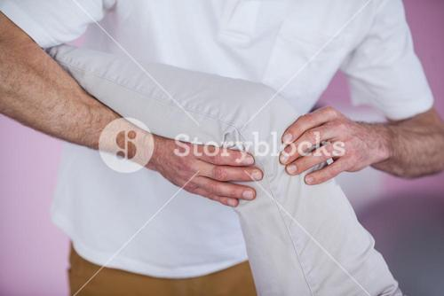 Mid section of physiotherapist giving leg massage to a patient