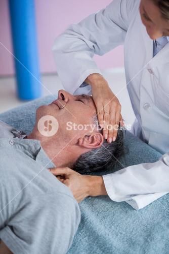 Senior man receiving neck massage from physiotherapist