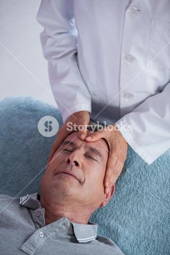 Senior man receiving head massage from physiotherapist