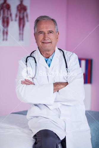 Portrait of physiotherapist sitting with arms crossed