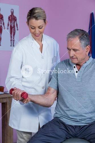 Physiotherapist assisting senior man to lift dumbbell
