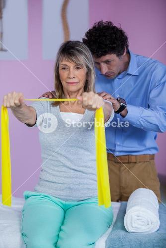 Senior woman training with exercise band assisted by physiotherapist