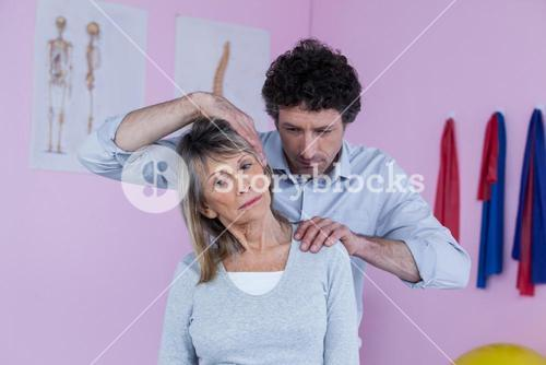 Physiotherapist giving shoulder massage to patient