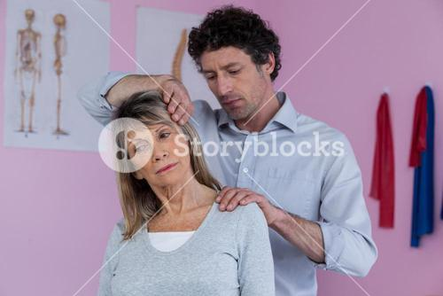 Physiotherapist giving neck massage to female patient