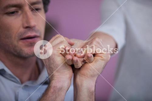 Physiotherapist giving hand massage to a patient