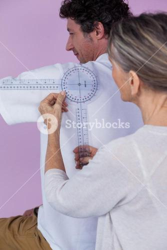 Physiotherapist measuring male patients back with medical ruler