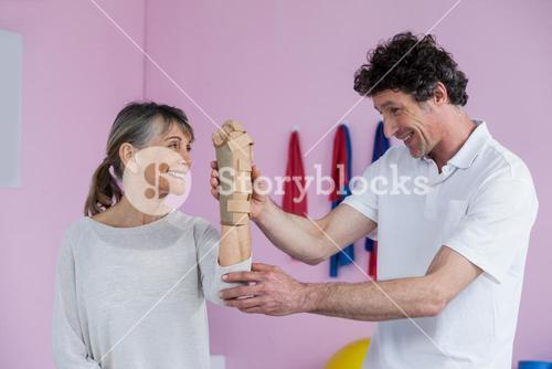 Physiotherapist examining a senior womans wrist