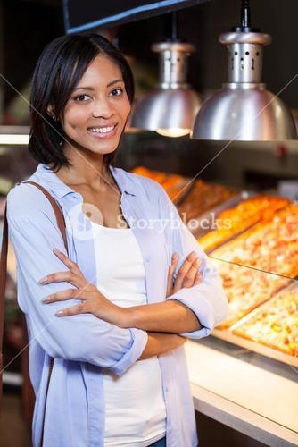 Happy woman standing at food counter