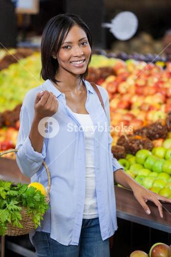 Smiling woman buying fruits in organic section