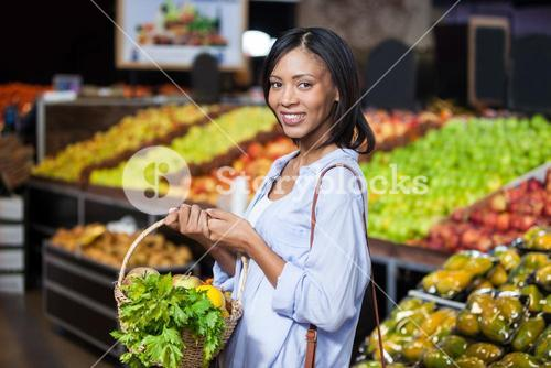 Smiling woman holding fruits and vegetables in basket