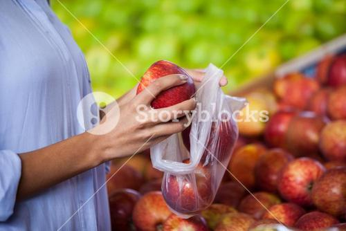 Woman buying an apple