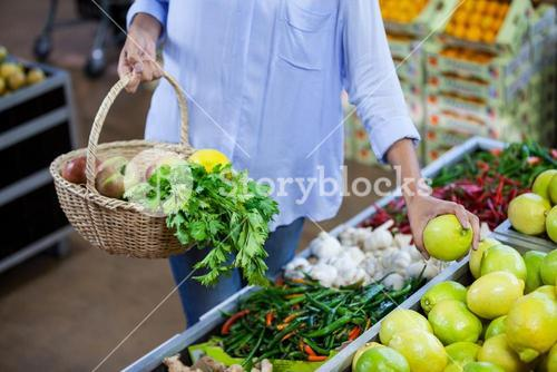 Woman buying sweet lime in organic section