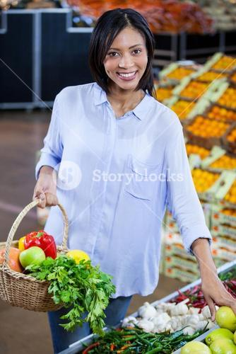 Woman buying vegetables and fruits in organic section
