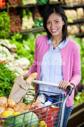 Woman holding trolley in organic section