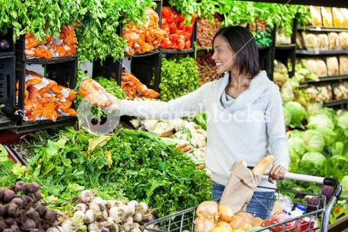 Woman buying carrot in organic section