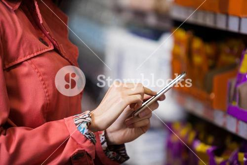 Mid section of woman using mobile phone
