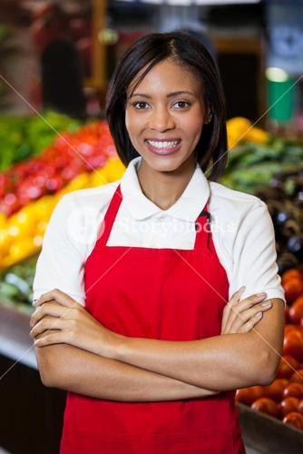Smiling female staff standing with arms crossed in organic section