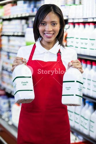 Female staff holding milk bottles in shelf