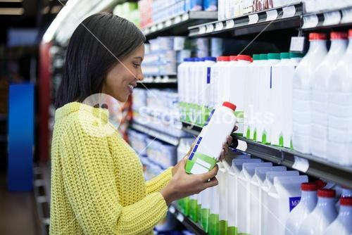 Woman looking milk bottle in dairy section