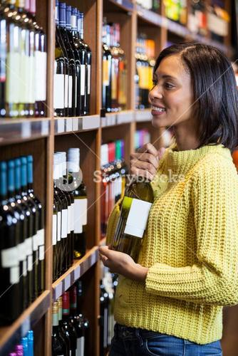 Woman selecting wine in grocery section