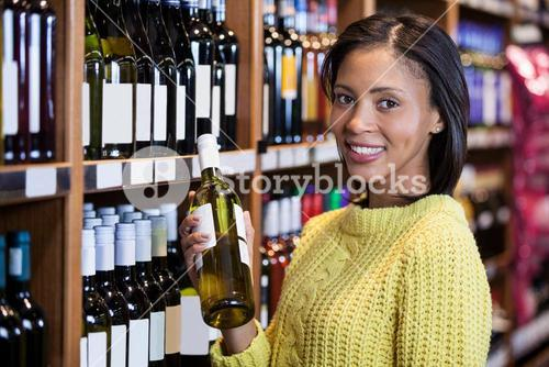 Woman holding wine bottle in grocery section