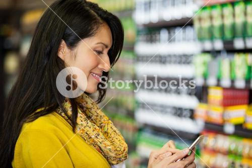 Woman using mobile phone in grocery section