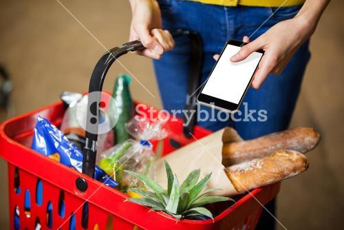 Woman holding groceries and mobile phone in supermarket