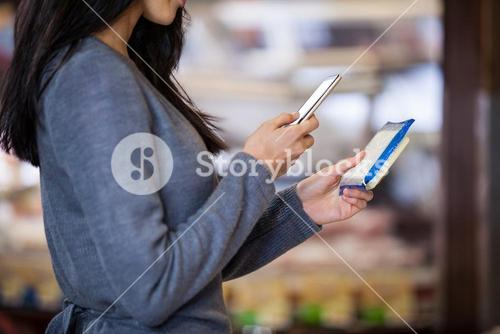 Woman holding dairy product and using mobile phone