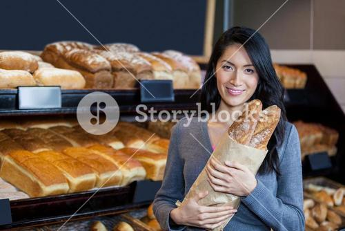 Woman holding baguettes in grocery bag