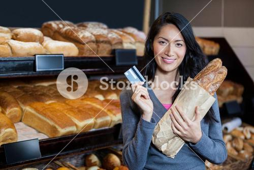 Woman holding baguettes and credit card at bread counter