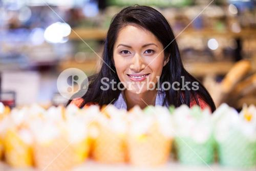 Portrait of woman looking at cupcakes