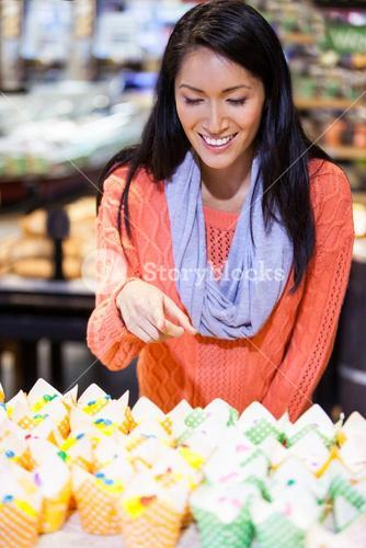 Excited woman looking at cupcakes