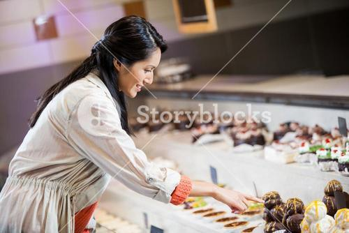 Happy woman selecting desserts
