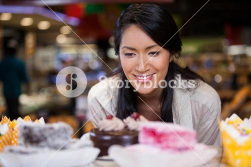 Happy woman selecting desserts from display