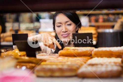 Woman selecting baguettes from bread counter