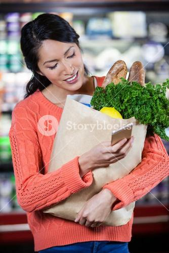 Woman using mobile phone while holding groceries