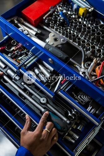 Mechanic selecting work tool from toolbox