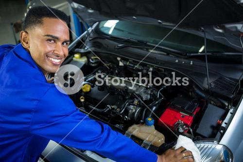 Happy mechanic servicing car